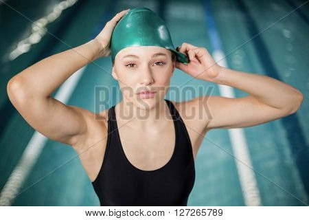 Pretty woman adjusting her bathing cap at the pool