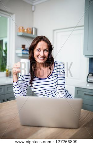 Portrait of smiling woman working on laptop while holding coffee mug at table in kitchen