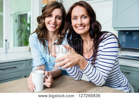 Portrait of smiling female friends holding coffee mugs while sitting at table in kitchen