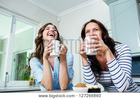Happy friends holding coffee mugs at table in kitchen
