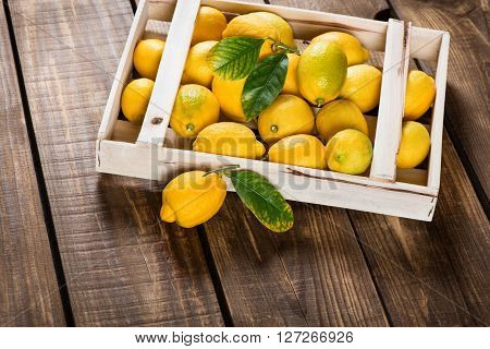 Lemons with green leaves in a crate with one on the surface in the foreground on wooden background.