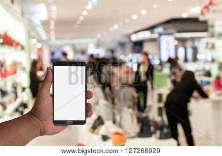 hand of man hold mobile phone over blurred image of people shopping in department store