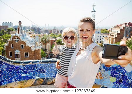 Smiling Mother And Baby Taking Selfie With Camera At Park Guell
