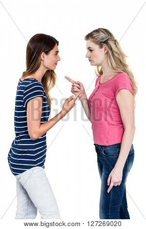 Female friends arguing while standing on white background