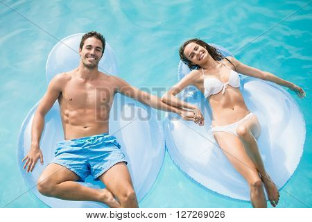 Portrait of happy couple relaxing on inflatable ring at swimming pool