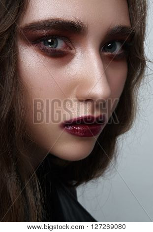 Beauty young female Rocker with dark red Makeup on perfect Skin