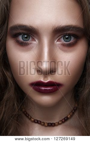 Biker or rocker beauty Girl with dark red Makeup and wooden Beads