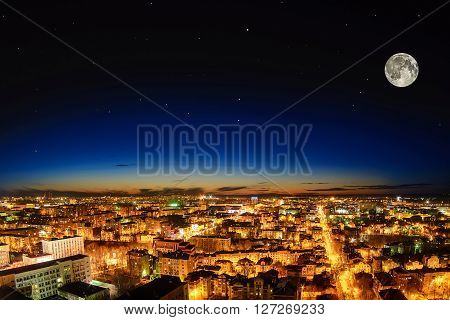 beautiful city at night from the height of the full moon with a clear starry sky at sunset