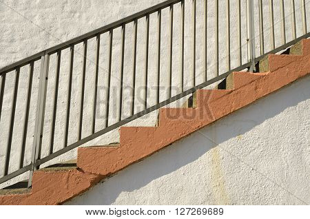 Staircase with metal railings against a whit wall, England UK