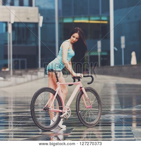Sexy girl on bicycle. Young slim sexy sportive woman in blue shorts and white snickers long-haired, sensual posing on pink fix bicycle at grey background in urban city enviroment. Instagram style