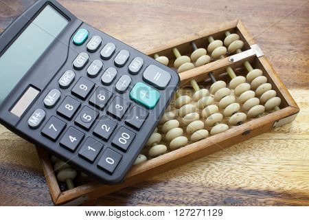 Abacus and calculator with wooden table background