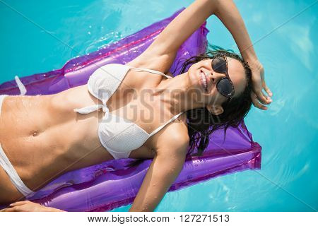High angle view of young woman relaxing on inflatable raft at swimming pool