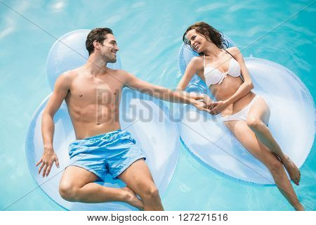 Happy young couple relaxing on inflatable ring at swimming pool