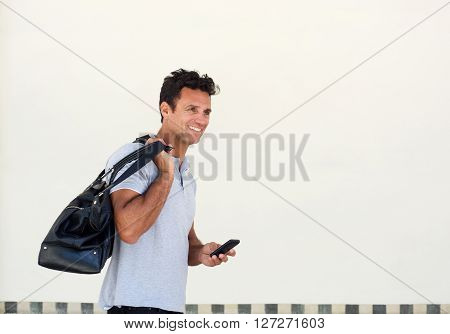 Handsome Older Man Walking With Bag And Mobile Phone