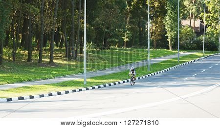 Female sportsman cyclist riding racing bicycle. Woman cycling on countryside summer road or highway. Training for triathlon or cycling competition. Wide angle.