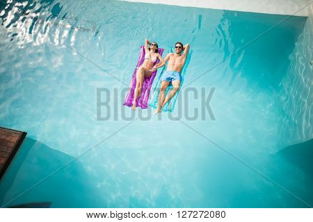 High angle view of couple relaxing on inflatable raft at swimming pool