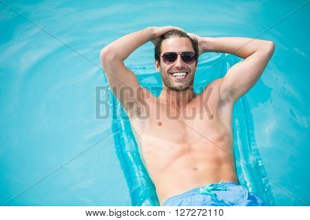 High angle view of cheerful man relaxing on inflatable raft at swimming pool