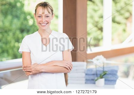 Portrait of confident female masseur with arms crossed standing at spa