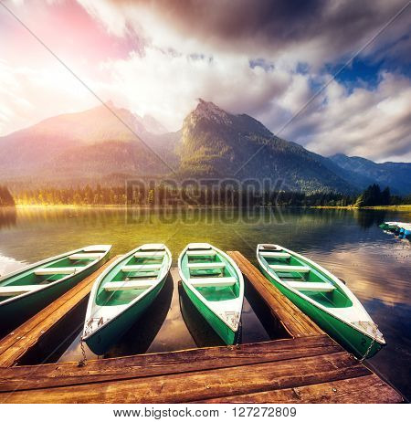 Fantastic views of the wooden pier that glows under sunlight. Dramatic and picturesque scene. Location famous resort National park Berchtesgadener Land, Hintersee, Bavarian Alps. Europe. Beauty world.