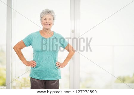 Portrait of smiling senior woman with hands on hip at home