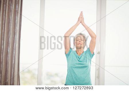 Senior woman performing yoga at home
