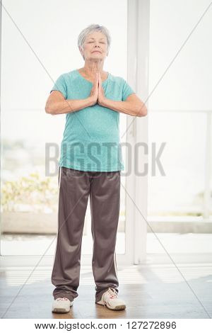 Senior woman with hands clasped performing yoga at home