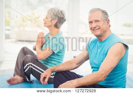 Portrait of smiling senior man sitting beside wife performing yoga at home