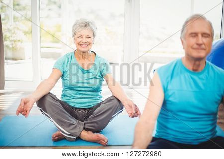 Portrait of happy senior woman with husband meditating at home