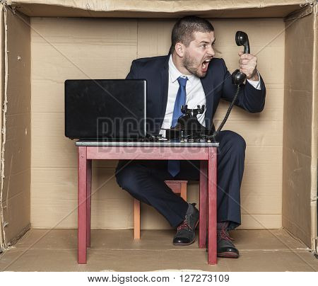 Angry Businessman At The Box Office Screaming To The Telephone Handset