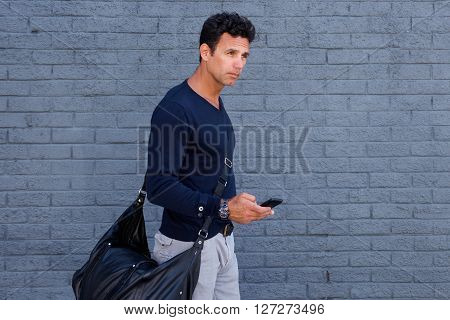 Male Traveler Walking With Mobile Phone And Bag