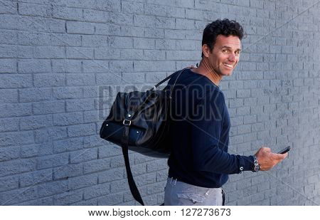 Man Turning Around Smiling With Bag And Mobile Phone