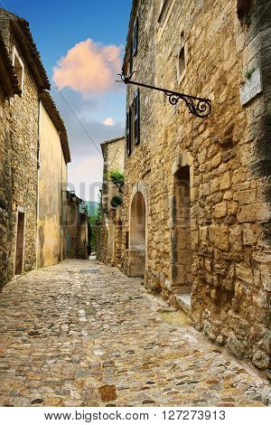 LACOSTE FRANCE - JUL 7 2014: Medieval street Rue de la Frescado in beautiful village of Lacoste at twilight. Lacoste is best known for its most notorious resident Donatien Alphonse Francois comte de Sade the Marquis de Sade