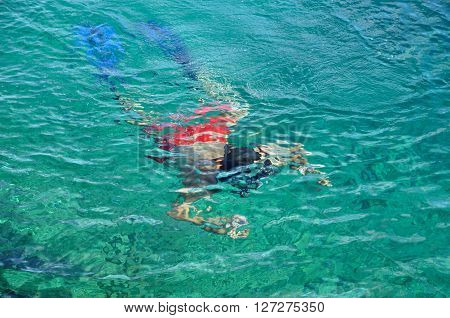 Snorkeling man in beautiful turquoise water in a tropical sea