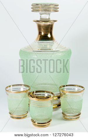 Green Glass Carafe And Three Glasses On White Background