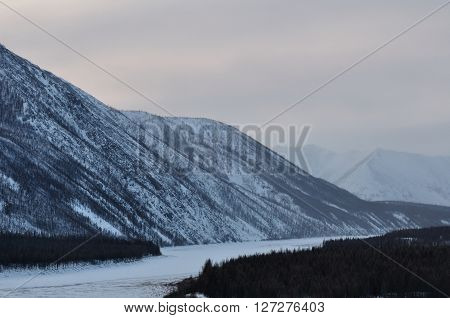 in winter, the frozen river, and mountains in the Taiga