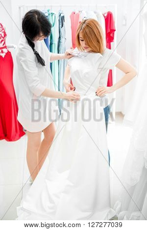the bride selects the wedding dress in the Studio. a young woman chooses a white dress in the store. salon of wedding dresses