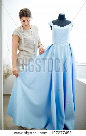 pretty young girl adjusts dress on the mannequin. blue dress on a mannequin. seamstress in a sewing workshop