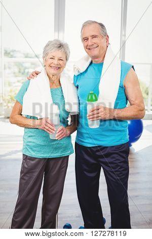 Portrait of smiling senior couple holding bottle while exercising