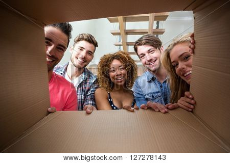 Portrait of cheerful friends seen through cardboard box at new house