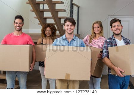 Portrait of friends smiling while carrying cardboard boxes in new house