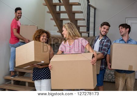 Cheeerful friends carrying cardboard boxes while relcocating in new house