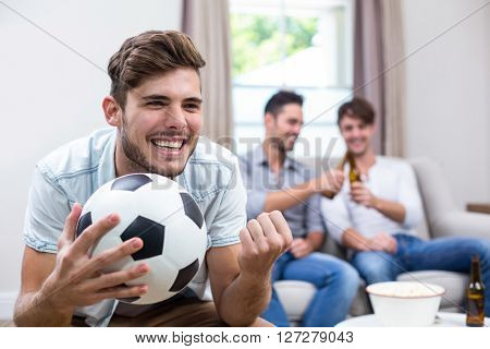 Close-up of happy young man watching soccer match while friends in background at home