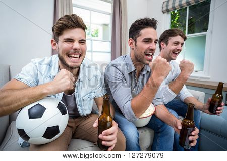 Close-up of cheerful male friends watching soccer match on TV at home