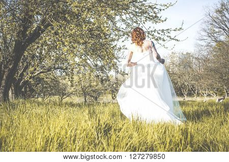 Bride running on meadow view from the back