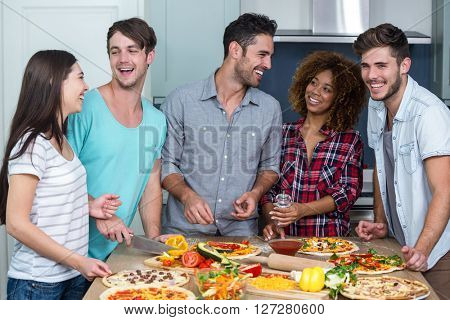 Cheerful multi-ethnic friends preparing pizza on kitchen table at home