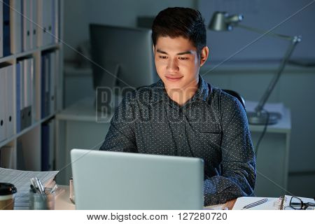Handsome young Filipino coder working in office till late night