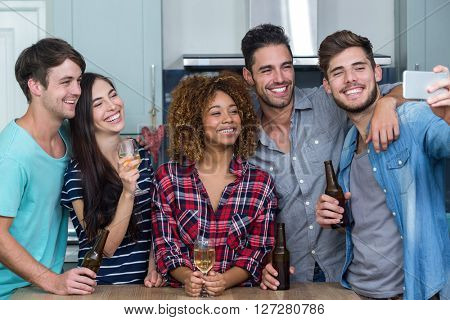 Cheerful multi-ethnic friends with alcohol taking selfie by table in kitchen