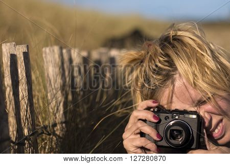 Young woman taking a photo in the country side with grass and wooden fence in the background
