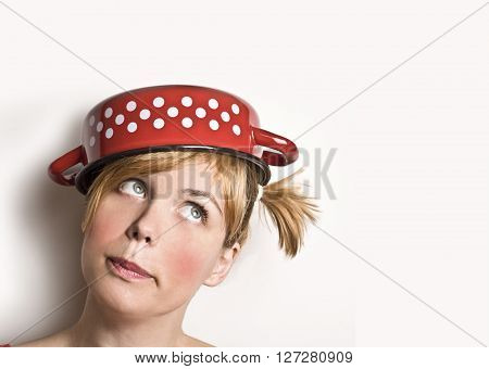 A beautiful young blonde woman with a small red dotted pan on her head looking up.