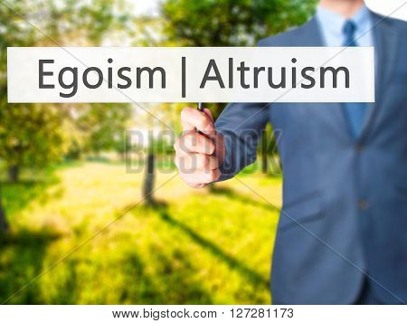 Altruism  Egoism - Businessman Hand Holding Sign